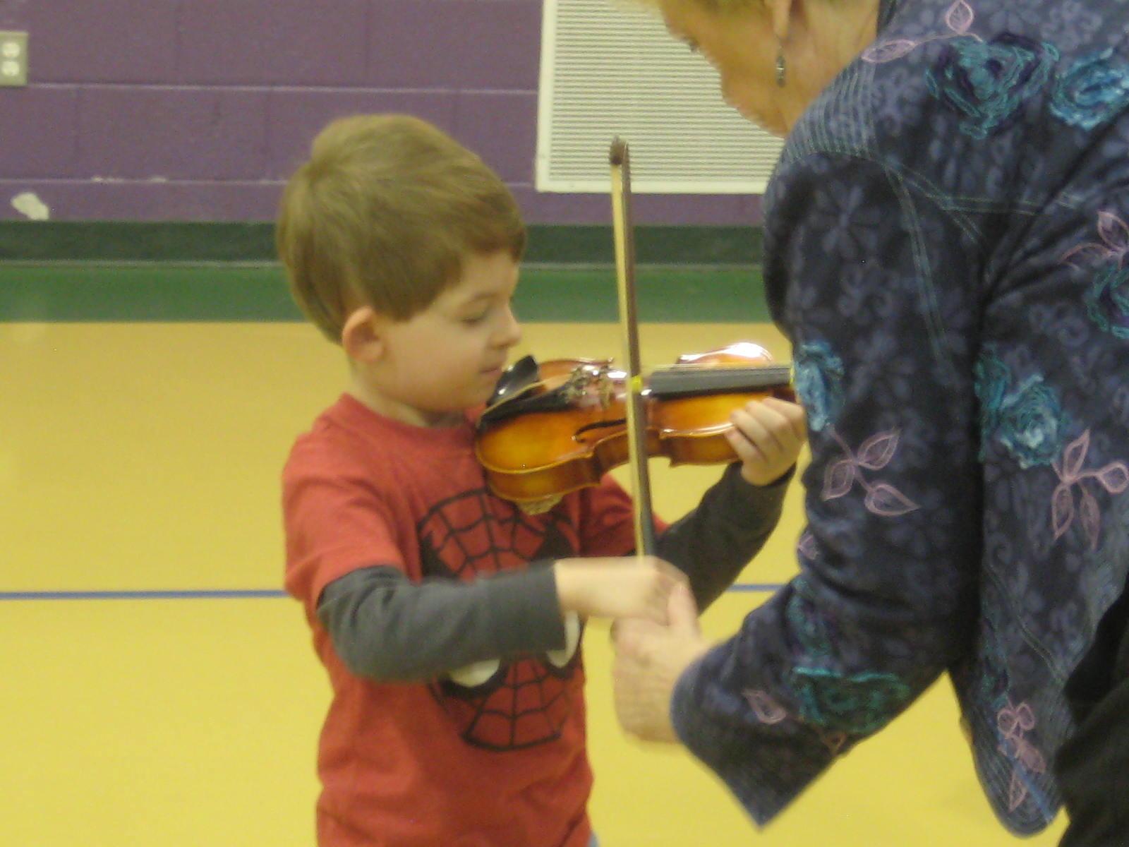 Lorraine Fink teaches violin to a Rosman Kindergarten  student